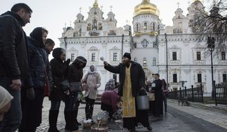 FILE - In this Sunday, April 8, 2018 file photo, a Ukrainian Orthodox priest blesses worshippers as they collect traditional cakes and painted eggs for an Easter celebration at the Kiev-Pechersk Lavra, the Monastery of the Caves, in Kiev, Ukraine. Ukraine is lobbying hard for a religious divorce from Russia and some observers say the issue could be decided as soon as September 2018. (AP Photo/Evgeniy Maloletka, File)