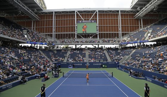 Evgeniya Rodina, of Russia, foreground, and Sloane Stephens warm-up to play in Louis Armstrong Stadium during the first round of the U.S. Open tennis tournament, Monday, Aug. 27, 2018, in New York. (AP Photo/Julio Cortez)