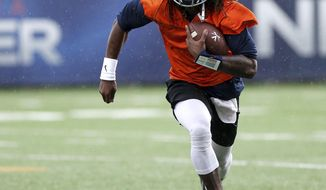 FILE - In this March 27, 2018, file photo, Virginia's Bryce Perkins runs the ball during the NCAA college football team's practice in Charlottesville, Va. Perkins has been praised as the answer at quarterback for Virginia. He enters his first week of game preparation of the Power Five level as the Cavaliers prepare to open against Richmond on Saturday. (Zach Wajsgras/The Daily Progress via AP, File)