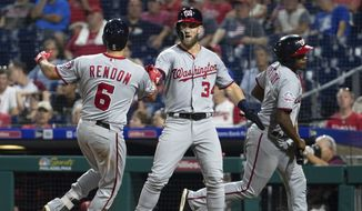 Washington Nationals' Bryce Harper, center, celebrates with Anthony Rendon, left, on his two-run home run during the ninth inning of a baseball game against the Philadelphia Phillies, Tuesday, Aug. 28, 2018, in Philadelphia. The Nationals won 5-4. (AP Photo/Chris Szagola)