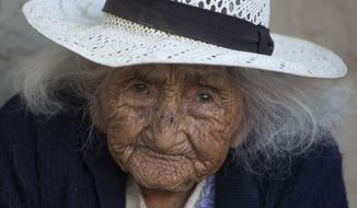 In this Aug. 23, 2018 photo, 117-year-old Julia Flores Colque eyes the camera while sitting outside her home in Sacaba, Bolivia. Her national identity card says Flores Colque was born on Oct. 26, 1900 in a mining camp in the Bolivian mountains. At 117 and just over 10 months, she would be the oldest woman in the Andean nation and perhaps the oldest living person in the world. (AP Photo/Juan Karita)