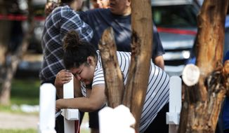 In this Sunday, Aug. 26, 2018, photo, Amber Ayala, who lost siblings in a fatal fire, hugs a wooden cross at the scene in Chicago. Several people were killed in the fire including multiple children. (Erin Hooley/Chicago Tribune via AP)