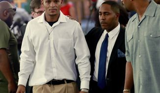 FILE - In this June 7, 2018, file photo, Robert Johnson, 35, left, leaves after his statement at New Beginnings Christian Church in Mesa, Ariz. Suburban Phoenix police officers shown on video beating an unarmed Johnson as he stood against a wall three months ago should not face criminal charges, outside police investigators said Monday, Aug. 27, 2018, about one of a series of recent incidents that drew questions about the agency's use of force. (AP Photo/Matt York, File)