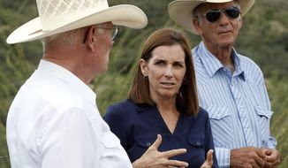 In this Wednesday, Aug. 22, 2018, U.S. Senatorial candidate U.S. Rep. Martha McSally, R-Ariz., stands at the international border with Mexico, with ranchers Jim Chilton, left, and Tom Kay, right, south of Arivaca, Ariz. In her bid to become the Republican Senate nominee, McSally has tacked hard right after initially keeping her distance from President Donald Trump. (AP Photo/Matt York)
