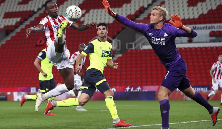 Stoke City's Saido Berahino, left, in action against Huddersfield Town's goalkeeper Jonas Lossl during their Carabao Cup, second round soccer match at the Bet365 Stadium, Stoke, England, Tuesday, Aug. 28, 2018. Saido Berahino, once one of the hottest young strikers in English soccer, ended a 2 1/2-year goal drought to help second-tier Stoke into the third round of the English League Cup at the expense of Premier League opposition. (Martin Rickett/PA via AP)