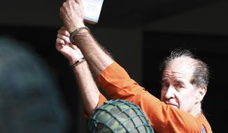 """Australian filmmaker James Ricketson holds a book with the title of """"The Faithful spy"""" upon his arrival at Phnom Penh Municipal Court in Phnom Penh, Cambodia, Tuesday, Aug. 28, 2018. Ricketson is on trial in Cambodia on charges of endangering national security by flying a drone over an opposition party rally last year. (AP Photo/Heng Sinith)"""
