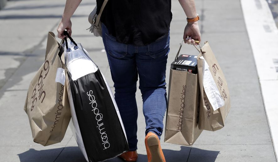 In this July 3, 2018, file photo, a shopper carries bags in San Francisco. On Tuesday, Aug. 28, the Conference Board releases its August index on U.S. consumer confidence. (AP Photo/Marcio Jose Sanchez, File)
