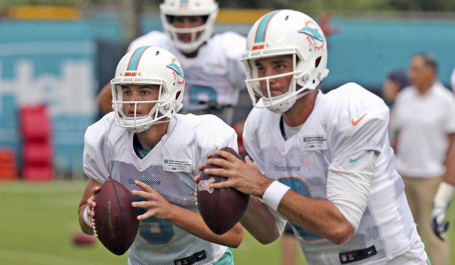 FILE - In this July 29, 2018, file photo, Miami Dolphins quarterbacks David Fales (9) and Brock Osweiler (8) run drills at NFL football training camp in Davie, Fla. The battle for the Dolphins' backup quarterback job between Brock Osweiler and David Fales will go down to the team's final exhibition game Thursday at Atlanta.(Charles Trainor Jr./Miami Herald via AP, File)