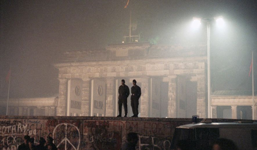 FILE - In this Nov. 14, 1989 file photo two East German border guards patrolled atop of Berlin Wall with the illuminated Brandenburg Gate in background, in Berlin.   (AP Photo/Jockel Finck, file)