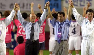 """FILE - In this Saturday, Sept. 7, 2002 file photo, South Korean national soccer team's head coach Park Hang-seo, second from left, and North Korean head coach Ri Jung-man, second from right, with the two team's players, raise their hands to South Korean soccer fans after their friendly match for unification of both Koreas, at the Sangam World Cup Stadium in Seoul, South Korea. If South Korea's national team is to reach the final of the Asian Games and win an exemption from military service for its players, then it will have to get past Vietnam and the """"Korean Hiddink."""" Korean coach Park Hang-seo, a member of Guus Hiddink's coaching staff at the 2002 World Cup when South Korea reached the semifinals, is coaching Vietnam. (AP Photo/ Yun Jai-hyoung)"""