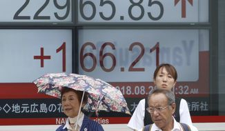 People stand in front of an electronic stock board of a securities firm in Tokyo, Tuesday, Aug. 28, 2018. Asian shares were mostly higher Tuesday after the White House said it reached a preliminary agreement with Mexico on replacing a North American free-trade deal. (AP Photo/Koji Sasahara)