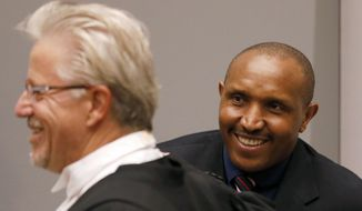 Bosco Ntaganda, a Congo militia leader, smiles toward his lawyer, left, in the courtroom of the International Criminal Court (ICC) during the closing statements of his trial in The Hague, Netherlands, Tuesday Aug. 28, 2018. Ntaganda is facing charges of war crimes and crimes against humanity allegedly committed in the eastern Ituri region of Congo from 2002-2003. (Bas Czerwinski/Pool via AP)