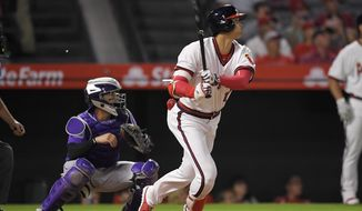 Los Angeles Angels' Shohei Ohtani, right, of Japan, hits a three-run home run as Colorado Rockies catcher Tony Wolters watches during the fourth inning of a baseball game Monday, Aug. 27, 2018, in Anaheim, Calif. (AP Photo/Mark J. Terrill)