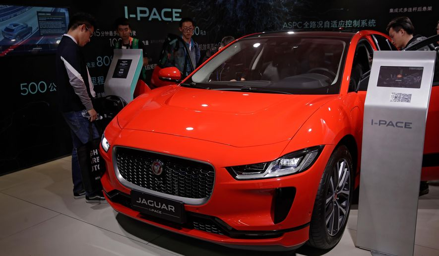 FILE- In this April 25, 2018, file photo journalists and visitors look at the Jaguar electric-powered I-Pace model showcases at the China Auto Show during the media day in Beijing. While Tesla grapples with internal issues like production delays, a sometimes-erratic CEO and a recent about-face on whether to go private, its rivals are moving aggressively into the luxury electric vehicle space. Jaguar Land Rover has the I-Pace.  (AP Photo/Andy Wong, File)