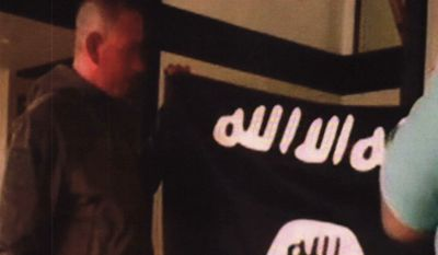 FILE - In this July 8, 2017 file image taken from FBI video and provided by the U.S. Attorney's Office in Hawaii on July 13, 2017, Army Sgt. 1st Class Ikaika Kang holds an Islamic State group flag after allegedly pledging allegiance to the terror group at a house in Honolulu. Newly unsealed court documents from an investigation into the Hawaii-based Army soldier accused of attempting to support the Islamic State group, provides more details about his obsession with the group's violence. (FBI/U.S Attorney's Office, District of Hawaii via AP, File)