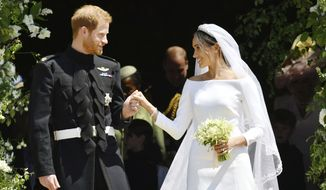 In this Saturday, May 19, 2018, file photo, Britain's Prince Harry and Meghan Markle stand on the steps of St. George's Chapel in Windsor Castle in Windsor, near London, England, after their wedding ceremony. The outfits Prince Harry and Meghan Markle wore at their wedding are to go on public display from Oct. 26, 2018 at the ceremony's venue, Windsor Castle. (Ben Birchhall/pool photo via AP, File)