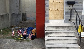 FILE - In this Nov. 27, 2017, file photo, a makeshift memorial sits in an alley where Baltimore Police Detective Sean Suiter was shot while investigating a 2016 triple homicide in Baltimore. The gunshot wound that killed Suiter one day before he was to testify about police corruption was most likely self-inflicted, an investigative review board has concluded. (AP Photo/Patrick Semansky, File)