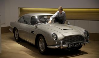 FILE - In this Tuesday, June 19, 2018 file photo, a staff member from the Bonhams motor car department poses for photographers with the 1965 Aston Martin DB5 driven by actor Pierce Brosnan in his role as James Bond in the 1995 movie GoldenEye during a photocall at premises of Bonhams auction house in London. Aston Martin, the maker of James Bond's favorite sports car, says it may sell shares for the first time as the company seeks to attract more wealthy buyers with an expanded product range including sedans, sports utility vehicles and even submarines. (AP Photo/Matt Dunham, File)