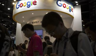 FILE - In this April 27, 2017, file photo, visitors use their smartphones in front of a booth for Google at the Global Mobile Internet Conference (GMIC) in Beijing. More than a dozen human rights groups have sent a letter dated Tuesday, Aug. 28, 2018, to Google urging the company not to offer censored internet search in China, amid reports it is planning to again begin offering the service in the giant Asian market. (AP Photo/Mark Schiefelbein, File)
