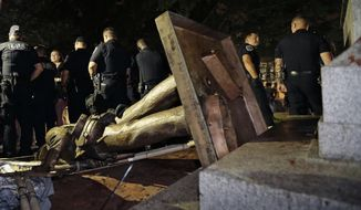 FILE - In this Monday, Aug. 20, 2018, file photo, police stand guard after the Confederate statue known as Silent Sam was toppled by protesters on campus at the University of North Carolina in Chapel Hill, N.C. A broadcast outlet reports a North Carolina police chief told his officers to stand aside as protesters tore down the Confederate monument. (AP Photo/Gerry Broome, File)