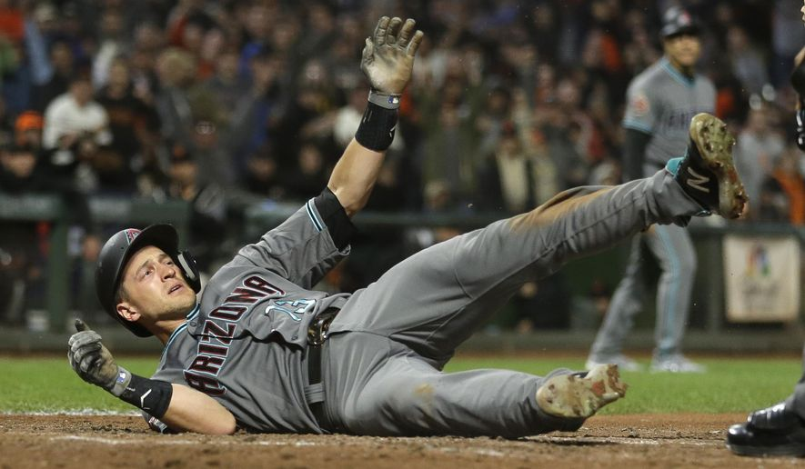 Arizona Diamondbacks' Nick Ahmed tumbles and waits for the call after being thrown out at home plate in the eighth inning of a baseball game against the San Francisco Giants, Tuesday, Aug. 28, 2018, in San Francisco. (AP Photo/Eric Risberg)