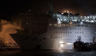 A firefighting vessel throws water as smoke rises from the Eleftherios Venizelos ship at the port of Piraeus, near Athen Wednesday, Aug. 29 2018. The passenger ferry with hundreds of passengers and crew arrived early Wednesday at the port of Piraeus after a fire broke out while the vessel was en route to the island of Crete, Greek coast guard said. (AP Photo/Petros Giannakouris)