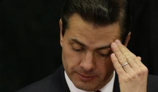 FILE - In this March 7, 2018 file photo, Mexican President Enrique Pena Nieto touches his head during an event focusing on women in honor of the upcoming Women's Day, at Los Pinos presidential residence in Mexico City. Pena Nieto has again defended on Wednesday, Aug. 29, the widely criticized original investigation of the 2014 disappearance of 43 students, but concedes that his administration has failed to bring the country peace.(AP Photo/Rebecca Blackwell, File)