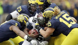 FILE - In this Nov. 25, 2017, file photo, Ohio State quarterback J.T. Barrett (16) is sacked by Michigan defensive linemen Rashan Gary (3) and Chase Winovich (15) during the second half of an NCAA college football game in Ann Arbor, Mich. When No. 12 Notre Dame has the ball Saturday night, No. 14 Michigan may have the advantage. The Wolverines appear to be loaded on defense with NFL-caliber players up front, at linebacker and in the secondary. (AP Photo/Carlos Osorio, File)