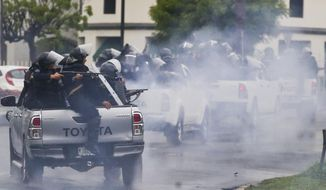 In this May 28, 2018, file photo, police in riot gear riding on the back of pick-up trucks fire their shotguns toward university students protesting Nicaragua's President Daniel Ortega in Managua, Nicaragua. More than 300 people have been killed in violence since mid-April. (AP Photo/Esteban Felix, File)