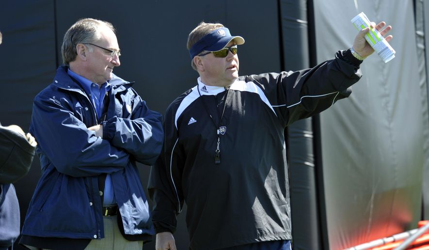 FILE - In this March 26, 2010, file photo, Notre Dame athletic director Jack Swarbrick, left, talks with head football coach Brian Kelly during his first NCAA college football practice in South Bend, Ind. Notre Dame coach Brian Kelly and athletic director Jack Swarbrick begin their ninth season together, leading the most scrutinized program in college football, when the 12th-ranked Fighting Irish face No. 14 Michigan on Saturday night, Sept. 1, 2018 . Only four Power Five schools have had the same combination of football coach and AD longer than Notre Dame. (AP Photo/Joe Raymond, File)