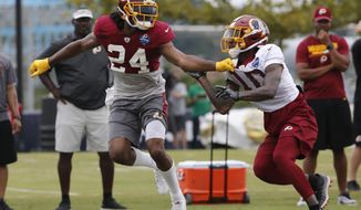 File- This July 31, 2018, file photo shows Washington Redskins defensive back Josh Norman (24) covering wide receiver Paul Richardson (10) during the morning session at NFL football training camp in Richmond, Va. Norman is going into the third year of a $75 million contract with just three interceptions for the Redskins and none last season. His abilities as a cover cornerback are unquestioned and mean he gets fewer opportunities, but Norman also dropped a handful of potential interceptions in 2017 and is being counted on, and paid, to make that kind of a difference in a young secondary.  (AP Photo/Steve Helber, File)