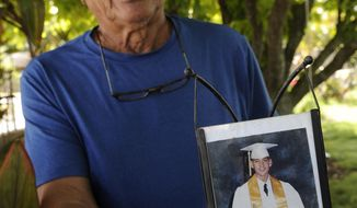 FILE - In this Monday, July 10, 2017 file photo, Clifford Kang, father of soldier Ikaika Kang, poses with a 2001 photo of his son in Kailua, Hawaii. Ikaika Kang is set to plead guilty Wednesday, Aug. 29, 2018, as charged in an indictment last year, defense attorney Birney Bervar said. He is agreeing to a 25-year sentence for charges that could have put him in prison for life. (Bruce Asato/Honolulu Star-Advertiser via AP, File)