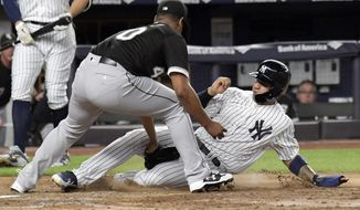 Chicago White Sox pitcher Reynaldo Lopez tags out New York Yankees runner Gleyber Torres, right, attempting to score when the ball got away from catcher Kevan Smith during the fifth inning of a baseball game Wednesday, Aug. 29, 2018, at Yankee Stadium in New York. (AP Photo/Bill Kostroun)