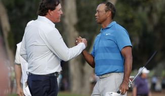 "FILE - In this May 10, 2018, file photo, Phil Mickelson, left, and Tiger Woods shake hands after the first round of the Players Championship golf tournament, in Ponte Vedra Beach, Fla.  The winner-take-all match between Tiger Woods and Phil Mickelson is on.  WarnerMedia says it has secured the rights for a pay-per-view event it is promoting as ""The Match."" It will be 18 holes between Woods and Mickelson held Thanksgiving weekend at Shadow Creek in Las Vegas. The winner will receive $9 million. The pay-per-view cost is to be announced later. (AP Photo/Lynne Sladky, File)"