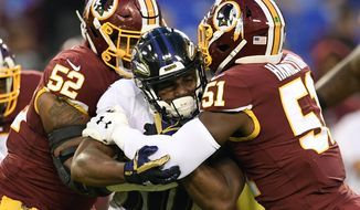 Washington Redskins linebackers Ryan Anderson (52) and Shaun Dion Hamilton (51) tackle Baltimore Ravens running back Kenneth Dixon who was rushing the ball in the first half of a preseason NFL football game Thursday, Aug. 30, 2018, in Baltimore. (AP Photo/Nick Wass)