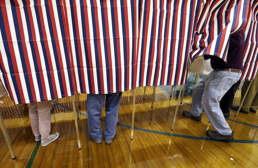 A voter enters a booth, Tuesday, Nov. 8, 2016, at a polling place in Exeter, N.H. (AP Photo/Elise Amendola)
