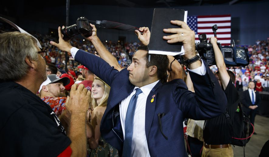 A volunteer member of the advance team for President Donald Trump blocks a camera as a photojournalist attempts to take a photo of a protester during a campaign rally at the Ford Center, Thursday, Aug. 30, 2018, in Evansville, Ind. (AP Photo/Evan Vucci)