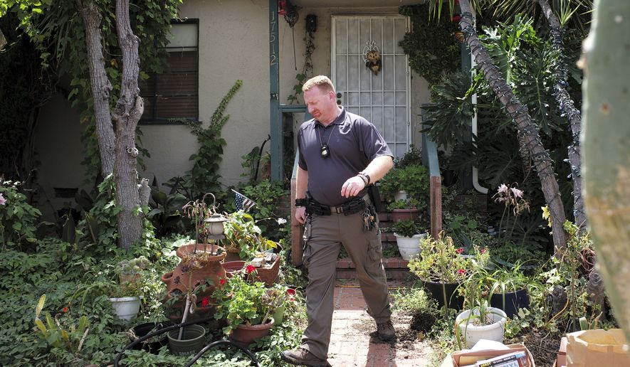 """An FBI agent leaves the home of Robert Chain in the Encino section of Los Angeles on Thursday, Aug. 30, 2018. Chain who was upset about The Boston Globe's coordinated editorial response to President Donald Trump's attacks on the news media, was arrested Thursday for threatening to travel to the newspaper's offices and kill journalists, whom he called the """"enemy of the people,"""" federal prosecutors said. (David Crane/Los Angeles Daily News via AP)"""