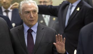 Brazils' President Michel Temer greets the media as he arrives for an update on the federal security intervention in Rio de Janeiro, Brazil, Thursday, Aug.30, 2018. (AP Photo/Silvia Izquierdo)