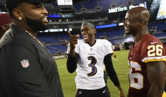 Baltimore Ravens quarterback Robert Griffin III, center, chats with Washington Redskins running back Adrian Peterson (26) after a preseason NFL football game, Thursday, Aug. 30, 2018, in Baltimore. (AP Photo/Nick Wass)