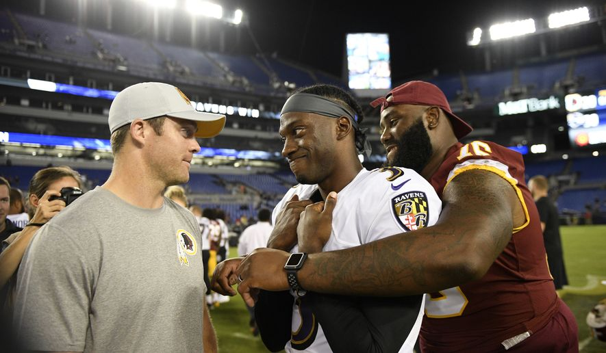 Baltimore Ravens quarterback Robert Griffin III, center, chats with Washington Redskins quarterback Colt McCoy, left, and offensive tackle Morgan Moses after a preseason NFL football game, Thursday, Aug. 30, 2018, in Baltimore. (AP Photo/Nick Wass)