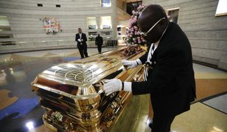 Vincent Street wipes down the casket of legendary singer Aretha Franklin at the Charles H. Wright Museum of African American History in Detroit, Wednesday, Aug. 29, 2018. Franklin died Aug. 16, 2018, of pancreatic cancer at the age of 76. (AP Photo/Paul Sancya)