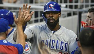 Chicago Cubs' Jason Heyward is congratulated in the dugout after scoring against the Atlanta Braves during the second inning of a baseball game Thursday, Aug. 30, 2018, in Atlanta. (AP Photo/John Amis)