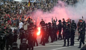 """In this Aug 27, 2018, file photo protesters light fireworks during a far-right demonstration in Chemnitz, Germany, after a man has died and two others were injured in an altercation between several people of """"various nationalities"""" in the eastern German city of Chemnitz on Sunday. (AP Photo/Jens Meyer, file)"""