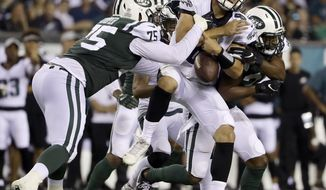 Philadelphia Eagles' Christian Hackenberg (8) fumbles the ball while being tackled by New York Jets' J.J. Wilcox (37) and Xavier Cooper (75) during the second half of a preseason NFL football game Thursday, Aug. 30, 2018, in Philadelphia. (AP Photo/Matt Rourke)