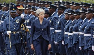 Britain's Prime Minister Theresa May inspects the honour guard after arriving to meet with Kenya's President Uhuru Kenyatta at State House in Nairobi, Kenya Thursday, Aug. 30, 2018. The British prime minister is on a three-country Africa visit with a large business delegation as Britain seeks to boost economic ties ahead of a bumpy exit from the European Union in March. (AP Photo/Ben Curtis)