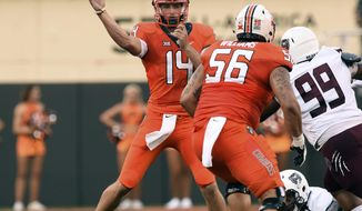 Oklahoma state quarterback Taylor Cornelius (14) throws a pass over teammate and offensive lineman Larry Williams (56) while under pressure from Missouri State defensive tackle Kylin Washington (99) during the first quarter of an NCAA college football game in Stillwater, Okla., Thursday, Aug. 30, 2018. (AP Photo/Brody Schmidt)