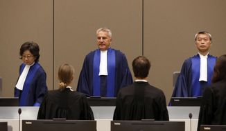 Presiding Judge Robert Fremr, center, stands in the courtroom of the International Criminal Court (ICC) during the closing statements of the trial of Bosco Ntaganda, a Congo militia leader, in The Hague, Netherlands, Tuesday Aug. 28, 2018. Ntaganda is facing charges of war crimes and crimes against humanity allegedly committed in the eastern Ituri region of Congo from 2002-2003. (Bas Czerwinski/Pool via AP) ** FILE **