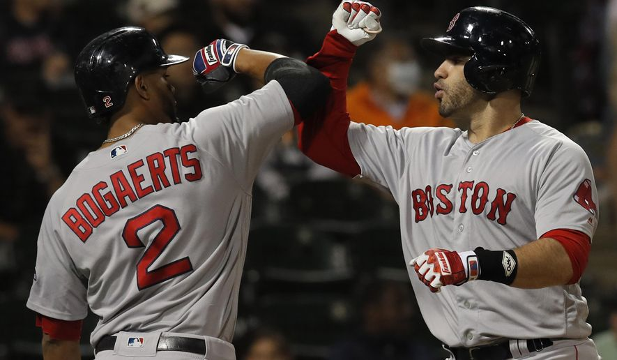 Boston Red Sox's J.D. Martinez, right, celebrates a three-run home run against the Chicago White Sox with teammate Xander Bogaerts during the ninth inning of a baseball game Thursday, Aug. 30, 2018, in Chicago. (AP Photo/Jim Young)