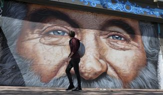 In this photo taken Wednesday, Aug. 29, 2018, a man walks past a new mural of Robin Williams on Market Street in San Francisco. Argentine muralist Andres Iglesias is paying tribute to the late Williams with the giant mural that depicts his blue eyes and nose framed by silver hair. The San Francisco Examiner reports Iglesias, who signs his art with the pseudonym Cobre, completed his wall-sized tribute to Williams on Sunday in the city's Tenderloin neighborhood. The artist says he picked Williams because he inspired him as a child. (AP Photo/Eric Risberg)